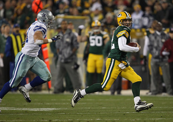 GREEN BAY, WI - NOVEMBER 07: Aaron Rodgers #12 of the Green Bay Packers runs for a first down pursued by Keith Brooking #51 of the Dallas Cowboys at Lambeau Field on November 7, 2010 in Green Bay, Wisconsin. The Packers defeated the Cowboys 45-7.  (Photo