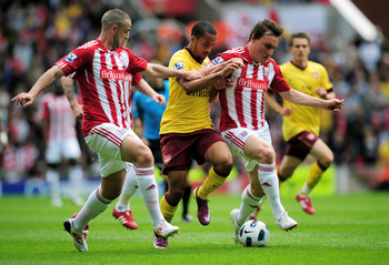 STOKE ON TRENT, ENGLAND - MAY 08:  Theo Walcott of Arsenal is closed down by Marc Wilson (L) and Dean Whitehead (R) of Stoke during the Barclays Premier League match between Stoke City and Arsenal at the Britannia Stadium on May 8, 2011 in Stoke on Trent,