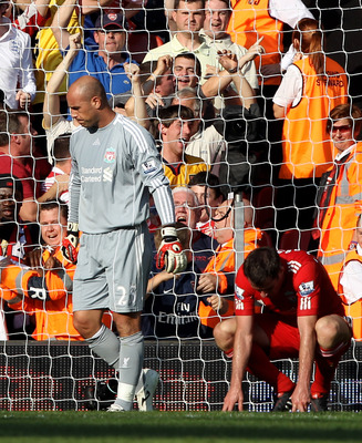 LIVERPOOL, ENGLAND - AUGUST 15:  Pepe Reina (L) of Liverpool reacts after scoring an own goal during the Barclays Premier League match between Liverpool and Arsenal at Anfield on August 15, 2010 in Liverpool, England.  (Photo by Clive Brunskill/Getty Imag