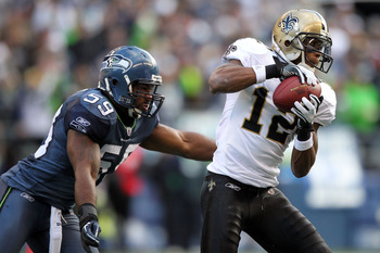 SEATTLE, WA - JANUARY 08:  Marques Colston #12 of the New Orleans Saints catches the ball against Aaron Curry #59 of the Seattle Seahawks in the first half during the 2011 NFC wild-card playoff game at Qwest Field on January 8, 2011 in Seattle, Washington