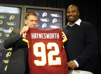 ASHBURN, VA - FEBRUARY 27:  Jim Zorn, head coach, presents Albert Haynesworth #92 with a team jersey after signing a 7-year contract worth approximately $100 million with the Washington Redskins on February 27, 2009 at Redskins Park in Ashburn, Virginia.