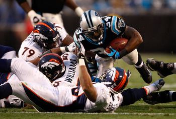 CHARLOTTE, NC - DECEMBER 14:  The defense of the Denver Broncos tries to stop DeAngelo Williams #34 of the Carolina Panthers during their game at Bank of America Stadium on December 14, 2008 in Charlotte, North Carolina  (Photo by Streeter Lecka/Getty Ima