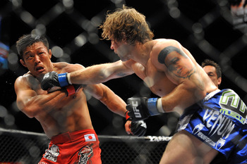 LAS VEGAS - JULY 11:  (R-L) Alan Belcher throws a right at Yoshihiro Akiyama during their middleweight bout during UFC 100 on July 11, 2009 in Las Vegas, Nevada.  (Photo by Jon Kopaloff/Getty Images)