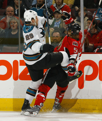 OTTAWA - FEBRUARY 26:  Ryan Clowe #29 of the San Jose Sharks throws a big hit on Brian Lee #55 of the Ottawa Senators along the far boards in a game on February 26, 2009 at the Scotiabank Place in Ottawa, Canada. (Photo by Phillip MacCallum/Getty Images)