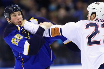 ST. LOUIS, MO - MARCH 24: B.J. Crombeen #26 of the St. Louis Blues fights Jean-Francois Jacques #22 of the Edmonton Oilers at the Scottrade Center on March 24, 2011 in St. Louis, Missouri.  (Photo by Dilip Vishwanat/Getty Images)