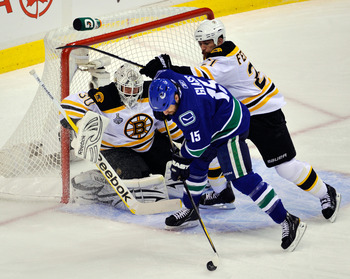 VANCOUVER, BC - JUNE 15:  Tim Thomas #30 of the Boston Bruins tends goal against Tanner Glass #15 of the Vancouver Canucks during Game Seven of the 2011 NHL Stanley Cup Final at Rogers Arena on June 15, 2011 in Vancouver, British Columbia, Canada.  (Photo