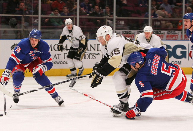 NEW YORK - JANUARY 25:  Sergei Gonchar #55 of the Pittsburgh Penguins battles for the puck against Dan Girardi #5 and Marc Staal #18 of the New York Rangers on January 25, 2010 at Madison Square Garden in New York City. Penguins defeated the Rangers 4-2.