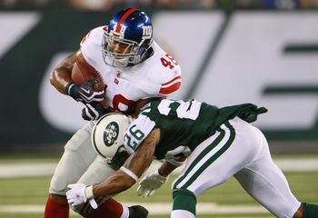 EAST RUTHERFORD, NJ - AUGUST 16:  Jerome Johnson #48 of the New York Giants attempts to break a tackle from Dwight Lowery #26 of the New York Jets during the preseason game at New Meadowlands Stadium on August 16, 2010 in East Rutherford, New Jersey. The