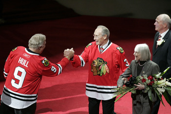 CHICAGO - NOVEMBER 12:  Former Chicago Blackhawks winger and NHL hall of famer Bobby Hull (L) shakes hands with fellow hall of famer and former Blackhawks defenseman Pierre Pilote (C), with his wife Anne, during a ceremony retiring Pilote and Keith Magnus