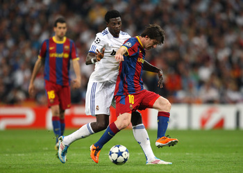 MADRID, SPAIN - APRIL 27:  Lionel Messi of Barcelona beats Emmanuel Adebayor of Real Madrid during the UEFA Champions League Semi Final first leg match between Real Madrid and Barcelona at Estadio Santiago Bernabeu on April 27, 2011 in Madrid, Spain.  (Ph