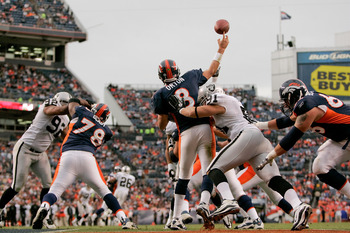 DENVER - OCTOBER 24:  Quarterback Kyle Orton #8 of the Denver Broncos is hit as he makes a pass from his own end zone by defensive end Trevor Scott #91 of the Oakland Raiders at INVESCO Field at Mile High on October 24, 2010 in Denver, Colorado. The Raide