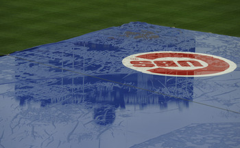 CHICAGO, IL - JULY 24:  The scoreboard is reflected on the tarp protecting the field from the rain before the start of the Houston Astros versus the Chicago Cubs game on July 24, 2011 at Wrigley Field in Chicago, Illinois.  (Photo by David Banks/Getty Ima