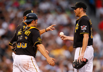 PITTSBURGH - AUGUST 02: Kevin Correia #29  of the Pittsburgh Pirates hands the ball off to manager Clint Hurdle #13 in front of Michael McKenry #55 after being pulled in the third inning after giving up 8 earned runs against the Chicago Cubs during the ga