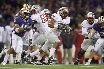 SEATTLE - NOVEMBER 28: Running back Dwight Tardy #31 of the Washington State Cougars rushes against Mason Foster #40 of the Washington Huskies on November 28, 2009 at Husky Stadium in Seattle, Washington. The Huskies defeated the Cougars 30-0. (Photo by O