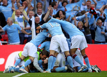 LONDON, ENGLAND - MAY 14:  Yaya Toure of Manchester City celebrates with his team mates after scoring the opening goal during the FA Cup sponsored by E.ON Final match between Manchester City and Stoke City at Wembley Stadium on May 14, 2011 in London, Eng