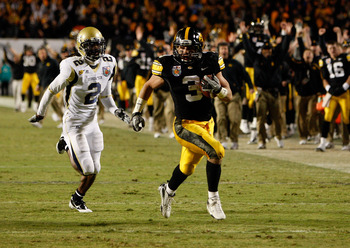 MIAMI GARDENS, FL - JANUARY 05:  Brandon Wegher #3 of the Iowa Hawkeyes scores a 32-yard rushing touchdown late in the fourth quarter against Mario Butler #2 of the Georgia Tech Yellow Jackets during the FedEx Orange Bowl at Land Shark Stadium on January