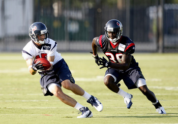 HOUSTON, TX - AUGUST 01:  Wide receiver  Jeff Maehl #15 of the Houston Texans completes a pass in front off cornerback Roc Carmichael #36 during practice on the first day of training camp at Reliant Park on August 1, 2011 in Houston, Texas.  (Photo by Bob