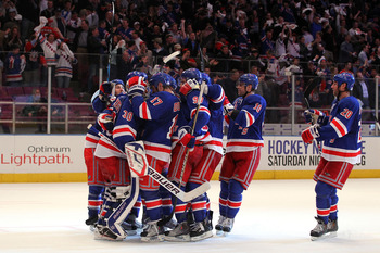 NEW YORK, NY - APRIL 17:  The New York Rangers surround goalie Henrik Lundqvist #30 as they celebrate their 3-2 win against the Washington Capitals in Game Three of the Eastern Conference Quarterfinals during the 2011 NHL Stanley Cup Playoffs at Madison S