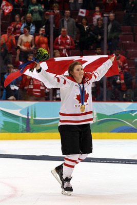 VANCOUVER, BC - FEBRUARY 25:  Team captain Hayley Wickenheiser #22 of Canada celebrates with her national flag after receiving the gold medal following her team's 2-0 victory during the ice hockey women's gold medal game between Canada and USA on day 14 o