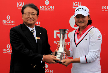 CARNOUSTIE, SCOTLAND - JULY 31:  Yani Tseng of Taiwan receives the trophy from Richo President & CEO Shiro Kondo  following her victory at the end of the final round of the 2011 Ricoh Women's British Open at Carnoustie Golf Links on July 31, 2011 in Carno