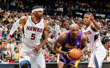 ATLANTA, GA - MARCH 08:  Lamar Odom #7 of the Los Angeles Lakers drives between Josh Smith #5 and Joe Johnson #2 of the Atlanta Hawks at Philips Arena on March 8, 2011 in Atlanta, Georgia.  NOTE TO USER: User expressly acknowledges and agrees that, by dow
