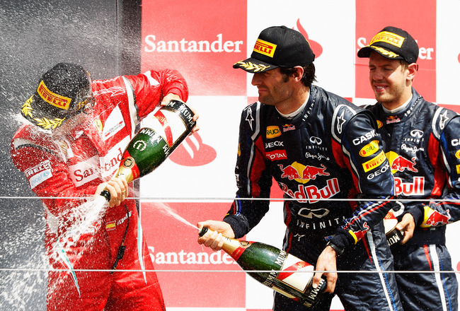 NORTHAMPTON, UNITED KINGDOM - JULY 10:  Race winner Fernando Alonso (L) of Spain and Ferrari celebrates on the podium with second placed Sebastian Vettel (R) of Germany and Red Bull Racing and third placed Mark Webber (C) of Australia and Red Bull Racing