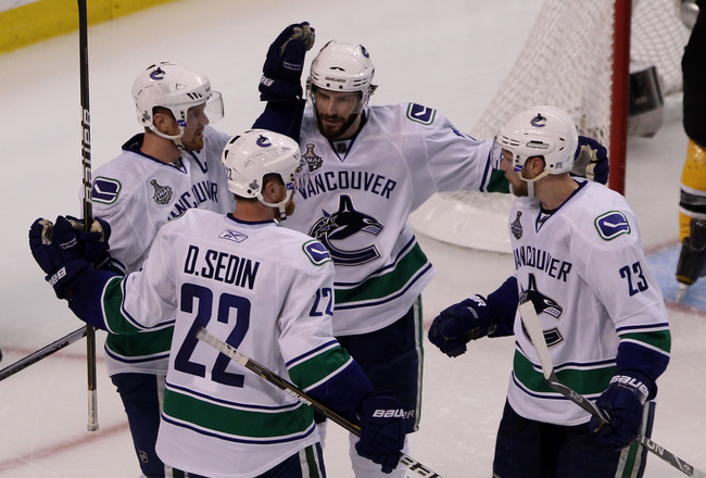 BOSTON, MA - JUNE 13:  Ryan Kesler #17 of the Vancouver Canucks celebrates with Henrik Sedin #33, Daniel Sedin #22 and Alexander Edler #23 against the Boston Bruins during Game Six of the 2011 NHL Stanley Cup Final at TD Garden on June 13, 2011 in Boston,