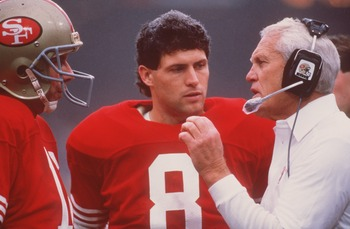 NOV 1987:  SAN FRANCISCO QUARTERBACK JOE MONTANA TALKS WITH HEAD COACH BILL WALSH, AS BACKUP QUARTERBACK STEVE YOUNG LISTENS, DURING THE 49ERS GAME AT CANDLESTICK PARK IN SAN FRANCISCO, CALIFORNIA. Mandatory Credit: Otto Greule/ALLSPORT