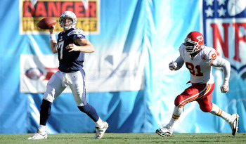 SAN DIEGO, CA - DECEMBER 12:  Philip Rivers #17 of the San Diego Chargers scrambles to throw from Tamba Hali #91 of the Kansas City Chiefs during the third quarter on way to a 31-0 Charger win at Qualcomm Stadium on December 12, 2010 in San Diego, Califor