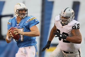 SAN DIEGO - DECEMBER 05:  Quarterback Philip Rivers #17 of the San Diego Chargers is chased out of the pocket by Richard Seymour #92 of the Oakland Raiders in the third quarter at Qualcomm Stadium on December 5, 2010 in San Diego, California. The Raiders