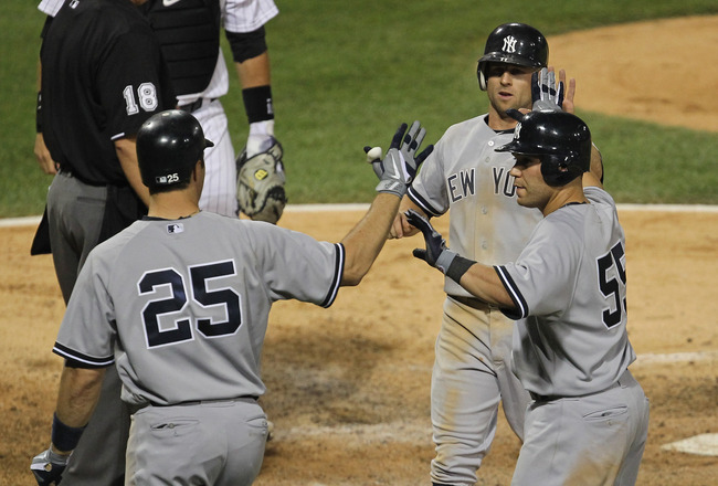 CHICAGO, IL - AUGUST 03: Mark Teixiera #25 of the New York Yankees greets teammates Russell Martin #55 and Brett Gardner #11 as they score runs in the 7th inning against the Chicago White Sox at U.S. Cellular Field on August 3, 2011 in Chicago, Illinois.