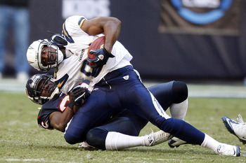 HOUSTON - NOVEMBER 07:  Tight-end Antonio Gates #85 of the San Diego Chargers is brought down by strong safety Eugene Wilson #26 of the Houston Texans at Reliant Stadium on November 7, 2010 in Houston, Texas.  (Photo by Bob Levey/Getty Images)