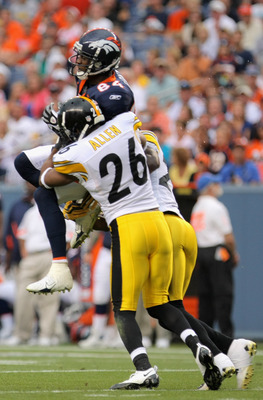 DENVER - AUGUST 29:  Wide receiver Brandon Lloyd #84 of the Denver Broncos makes a reception and is tackled by safety Will Allen #26 of the Pittsburgh Steelers during preseason NFL action at INVESCO Field at Mile High on August 29, 2010 in Denver, Colorad