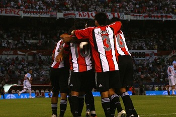 BUENOS AIRES, ARGENTINA - FEBRUARY 10:  Paulo Ferrari of River Plate is congratulated by team mates after scoring the second goal during the Primera Division closing season match between River Plate and Gimnasia de Jujuy at the Estadio Monumental on Febru