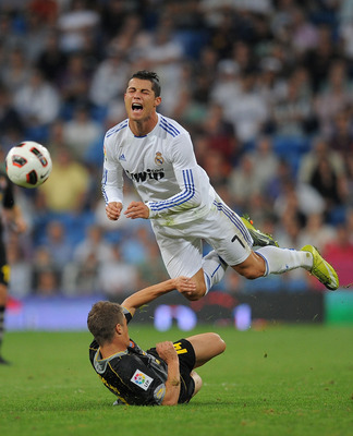 MADRID, SPAIN - SEPTEMBER 21:  Cristiano Ronaldo (L) of Real Madrid is fouled by Ernesto Galan of Espanyol during the La Liga match between Real Madrid and Espanyol at Estadio Santiago Bernabeu on September 21, 2010 in Madrid, Spain.  (Photo by Denis Doyl