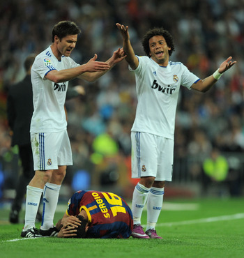 MADRID, SPAIN - APRIL 16: Xabi Alonso (L) and Marcelo of Real Madrid react after Sergio Busquets of Barcelona took a knock during the La Liga match between Real Madrid and Barcelona at Estadio Santiago Bernabeu on April 16, 2011 in Madrid, Spain.  (Photo