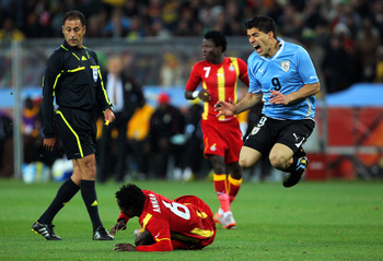 JOHANNESBURG, SOUTH AFRICA - JULY 02: Anthony Annan of Ghana clashes with Luis Suarez of Uruguay during the 2010 FIFA World Cup South Africa Quarter Final match between Uruguay and Ghana at the Soccer City stadium on July 2, 2010 in Johannesburg, South Af