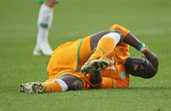 PORT ELIZABETH, SOUTH AFRICA - JUNE 15:  Emmanuel Eboue of Ivory Coast holds his ankle in pain during the 2010 FIFA World Cup South Africa Group G match between Ivory Coast and Portugal at Nelson Mandela Bay Stadium on June 15, 2010 in Port Elizabeth, Sou