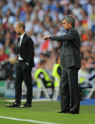 MADRID, SPAIN - APRIL 27:  Head coach Jose Mourinho (R) of Real Madrid stands backdropped by head coach Josep Guardiola of Barcelona during the UEFA Champions League Semi Final first leg match between Real Madrid and Barcelona at the Estadio Santiago Bern