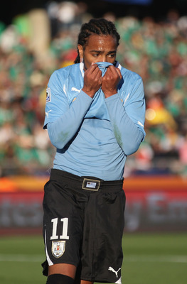RUSTENBURG, SOUTH AFRICA - JUNE 22:  Alvaro Pereira of Uruguay covers his face with his shirt during the 2010 FIFA World Cup South Africa Group A match between Mexico and Uruguay at the Royal Bafokeng Stadium on June 22, 2010 in Rustenburg, South Africa.