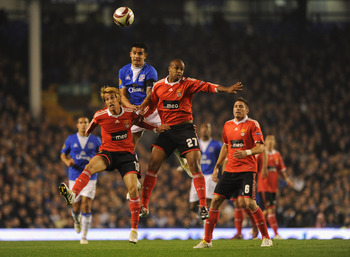 LIVERPOOL, ENGLAND - NOVEMBER 05:  Tim Cahill of Everton goes up for a header with Fabio Coentrao and Sidnei (R) of Benfica during the UEFA Europa League Group I match between Everton and Benfica at Goodison Park on November 5, 2009 in Liverpool, England.