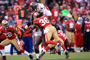 SAN FRANCISCO - NOVEMBER 21:  LeGarrette Blount #27 of the Tampa Bay Buccaneers leaps over Reggie Smith #30 when he is hit by Dashon Goldson #38 of the San Francisco 49ers at Candlestick Park on November 21, 2010 in San Francisco, California.  (Photo by E