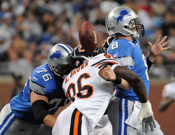 DETROIT - OCTOBER 05:  Alex Brown #96 of the Chicago Bears causes a fumble on a sack of Jon Kitna #8 of the Detroit Lions while defended by Jeff Backus #76 during the first quarter at Ford Field on October 5, 2008 in Detroit, Michigan.  The Bears won 34-7