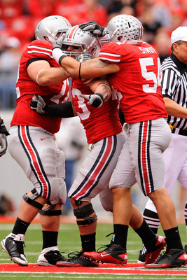 COLUMBUS, OH - OCTOBER 23:  Nathan Williams #43 of the Ohio State Buckeyes celebrates with Dexter Larimore #72 of the Ohio State Buckeyes and John Simon #54 of the Ohio State Buckeyes after making a tackle on fourth down against the Purdue Boilermakers at