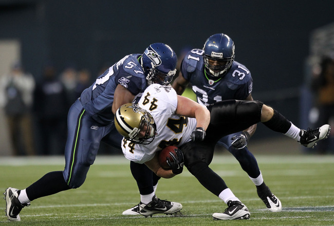 SEATTLE, WA - JANUARY 08:  Heath Evans #44 of the New Orleans Saints is tackled by David Hawthorne #57 and Kam Chancellor #31 of the Seattle Seahawks during the 2011 NFC wild-card playoff game at Qwest Field on January 8, 2011 in Seattle, Washington.  (Ph