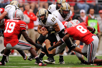 COLUMBUS, OH - OCTOBER 23:  Quarterback Rob Henry #15 of the Purdue Boilermakers looks for running room as Orhian Johnson #19 of the Ohio State Buckeyes and Aaron Gant #8 of the Ohio State Buckeyes close in for the tackle at Ohio Stadium on October 23, 20