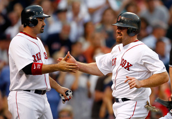 BOSTON, MA - AUGUST 3:  Kevin Youkilis #20 of the Boston Red Sox and Adrian Gonzalez #28 of the Boston Red Sox score in the first inning in a game with the Cleveland Indians at Fenway Park on August 3, 2011 in Boston, Massachusetts.  (Photo by Jim Rogash/