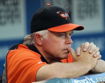 KANSAS CITY, MO - AUGUST 02:  Manager Buck Showalter #26 of the Baltimore Orioles watches from the dugout prior to the start of the game against the Kansas City Royals on August 2, 2011 at Kauffman Stadium in Kansas City, Missouri.  (Photo by Jamie Squire