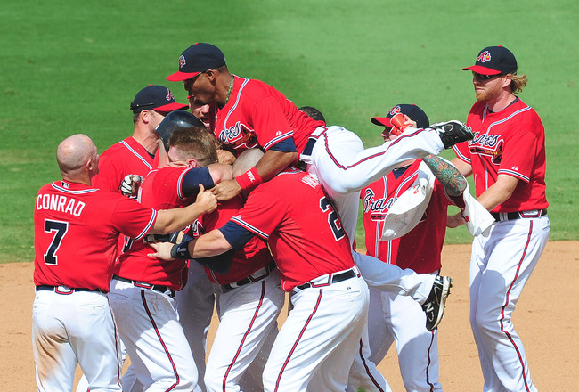 ATLANTA - JULY 17: Freddie Freeman #5 of the Atlanta Braves is mobbed by teammates after knocking in the winning run in the 9th inning against the Washington Nationals at Turner Field on July 17, 2011 in Atlanta, Georgia. (Photo by Scott Cunningham/Getty