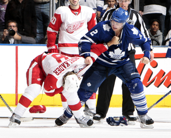 TORONTO - OCTOBER 2: Luke Schenn #2 of the Toronto Maple Leafs beats on Justin Abdelkader #8 of the Detroit Red Wings during a preseason NHL game at the Air Canada Centre October 2, 2010 in Toronto, Ontario, Canada. (Photo by Abelimages/Getty Images)